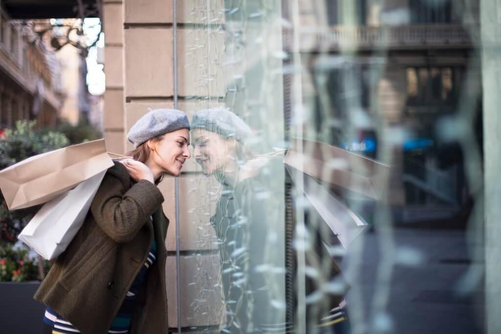 Mulher segurando sacola de compras olhando a vitrine