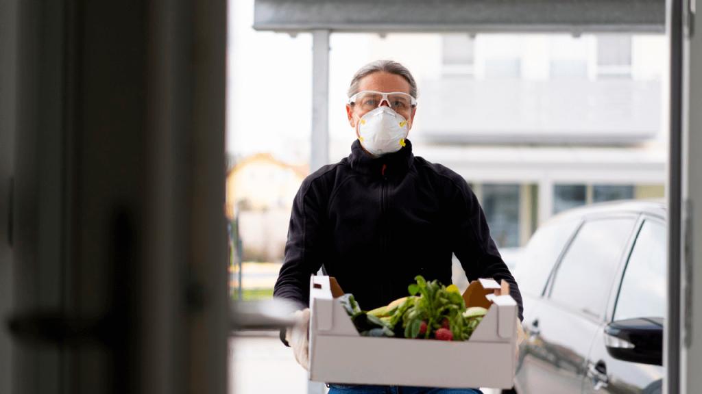 Homem usando máscara carrega uma caixa de entregas cheia de verduras.