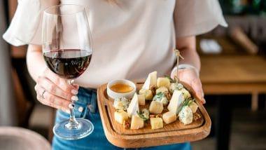 garota segurando uma tábua de queijos e uma taça de vinho